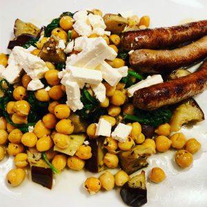 Stoof van kikkererwten, spinazie, aubergine, feta en chipolataworstjes